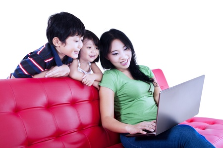 Happy asian mother and kids surfing the internet photo