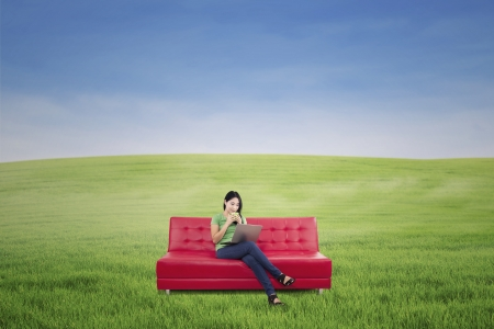 Beautiful female is relaxing on red sofa outdoor at green field photo