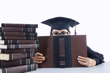 Portrait of graduating student girl covering her face on white background photo