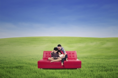 Portrait happy family sitting on a couch on a green meadow photo