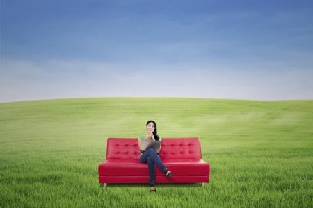 mujer pensativa: Mujer pensativa con caf� en el sof� rojo en campo verde al aire libre Foto de archivo