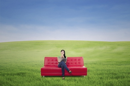 red sofa: Pensive woman having coffee on red sofa at green field outdoor Stock Photo