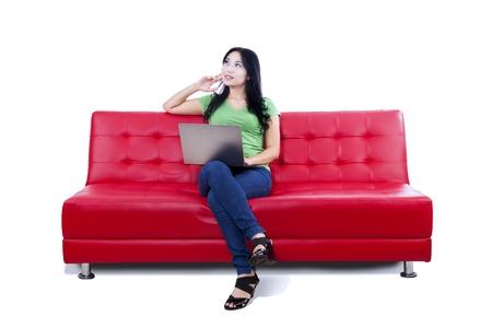 mujer pensativa: Mujer pensativa sentado en el sofá rojo con la computadora portátil, aislado en blanco