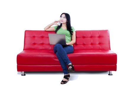 red sofa: Pensive woman sitting on red sofa with laptop, isolated on white