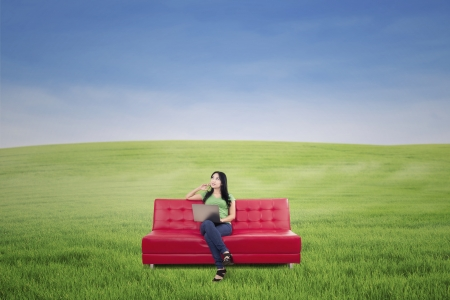 Pensive woman sitting on red sofa at green meadow Stock Photo - 20772469