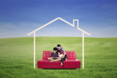 Young family seated on a sofa dreaming a home in the nature photo