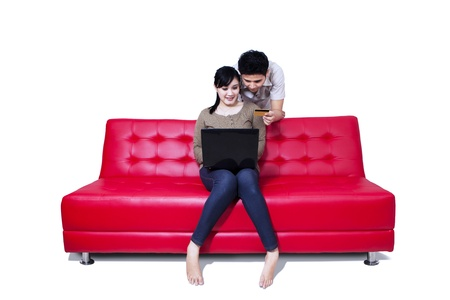 Asian couple sitting on red sofa paying online by credit card, isolated on white photo