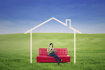 Asian woman is having coffee outdoor with dream house picture Stock Photo - 20911340