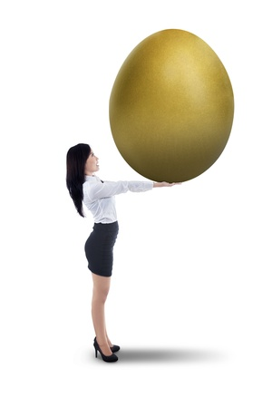 Asian businesswoman holding large golden egg on white background photo