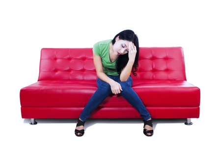 Attractive female is upset while sitting on red sofa on white background Stock Photo - 20922401