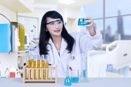 analysing: Beautiful female doctor is analysing chemical in flasks at the hospital