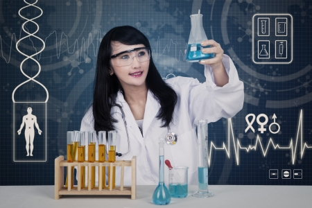 Beautiful female scientist analysing blue liquid in flask on blue background photo