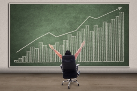 Business CEO with his arms raised looking at profit bar chart on chalkboard photo