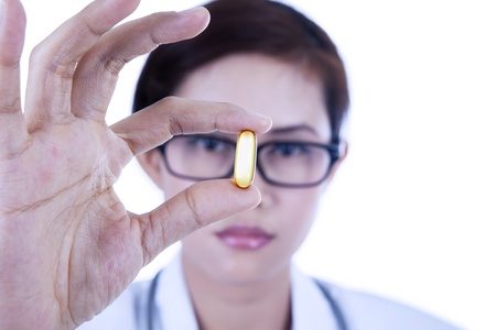 Close-up of a doctor holding oil capsule on white background photo