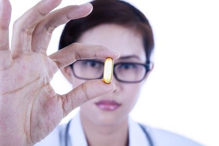 gelatina: Primer plano de un médico sosteniendo cápsula de aceite en el fondo blanco Foto de archivo