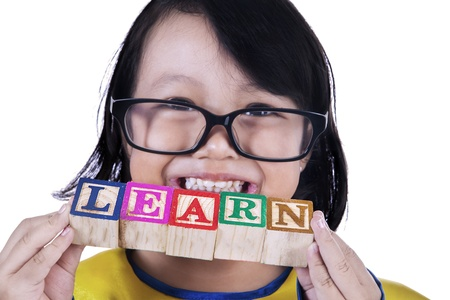 Close-up portrait of a girl holding LEARN wooden cube toy on white photo