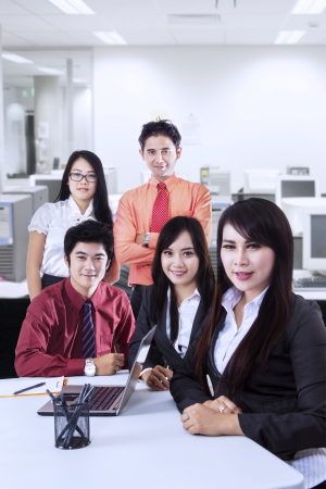 asian group: Team of five people posing at the office