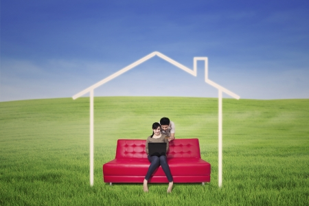 blue sky thinking: Asian couple is using laptop to search for dream house on green field Stock Photo