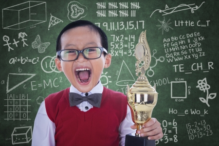 Excited boy screaming while holding trophy in class photo