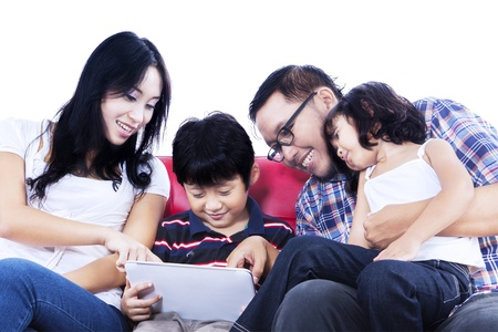 Isolated picture of family using touchpad on red sofa