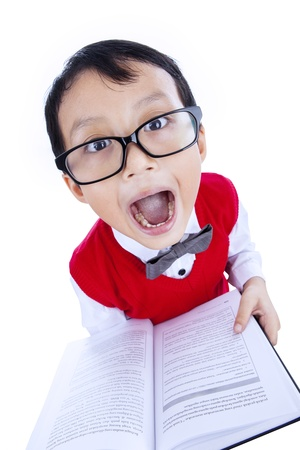 Funny expression of a nerd student boy holding a book on white background photo