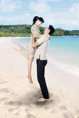 barefoot man: Asian couple is having fun at beach