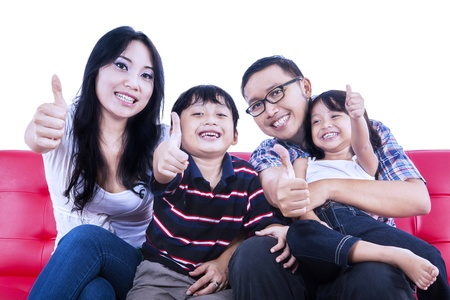 family sofa: Isolated picture of family members showing thumbs up on red sofa