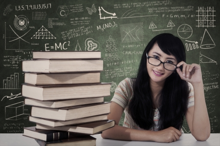 Beautiful female student study in class with stack of books photo