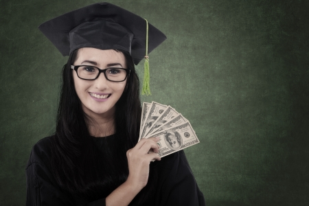 academic robe: Beautiful graduate student get money as a gift Stock Photo