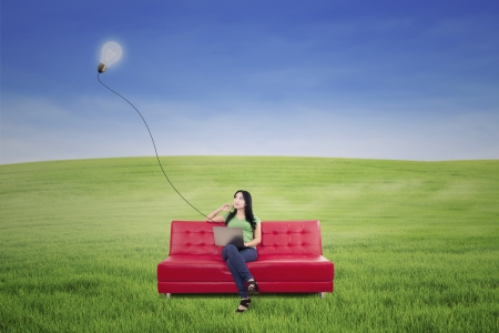 red sofa: Young woman with laptop thinking under lamp on green field