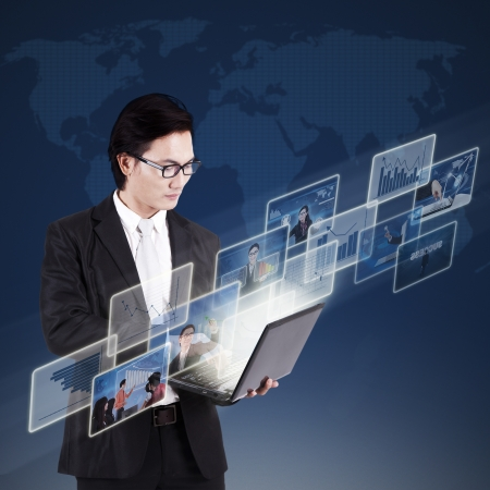 Asian businessman working on his laptop and searching online pictures on blue world map background photo