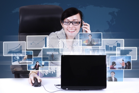 Businesswoman calling while choosing online pictures using laptop on blue world map background photo