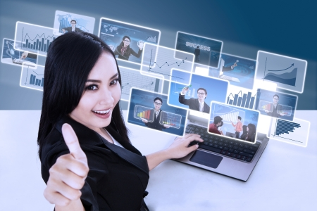 Happy businesswoman giving thumbs up with pictures interface in front of laptop on blue background photo