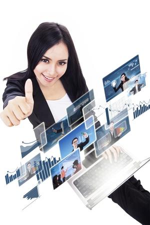 ラップトップ上で、白で隔離されるオンラインの写真を選択しながら親指を現して実業家