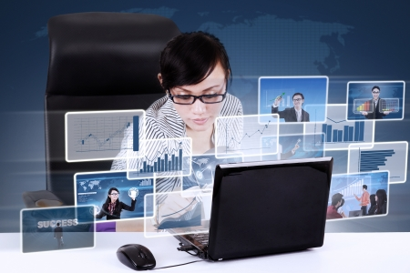 Asian businesswoman looking for online pictures worldwide on laptop Stock Photo - 20990596