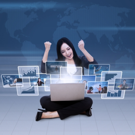 Excited businesswoman raised her arms looking at successful reports in laptop Stock Photo - 20990602