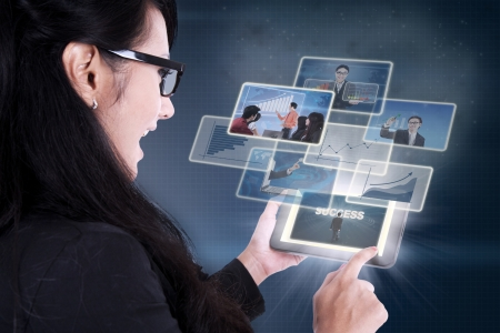 e pretty: Businesswoman excited looking at success pictures on electronic tablet Stock Photo