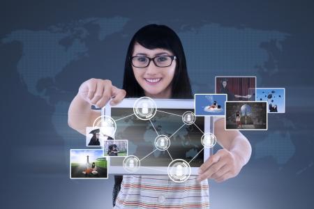 幸せな若い女性は青の世界地図接続と写真とタブレットを見せています。