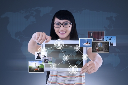 use computer: Happy young female is showing a tablet with world map connection and pictures on blue