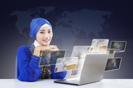 Happy female muslim in blue dress looking for online pictures at laptop on blue background photo