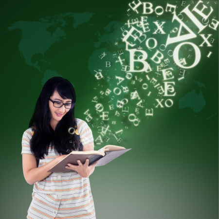 Happy female student reading book with alphabet letters flying out from it on green background photo