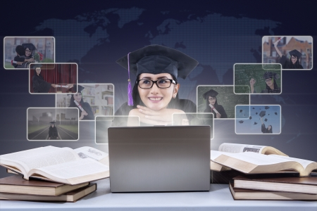 Happy female graduate with laptop and online pictures on world map background photo