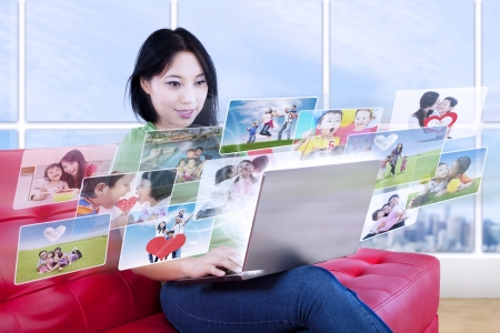 Beautiful female is looking at online photos in laptop inside an apartment photo