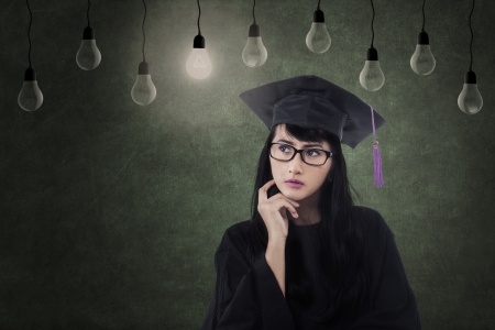 Beautiful Asian female graduate thinking of ideas in class under lamps photo
