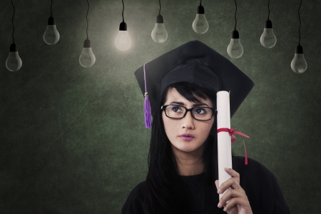 Beautiful female graduate with certificate under lamps and lit bulb photo