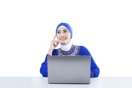 Beautiful female muslim is thinking with laptop on white photo