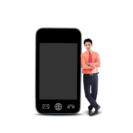 businessman standing: Businessman standing next to big smartphone on white background Stock Photo