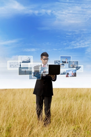 ultrabook: Businessman is looking at online photos on wheat field outdoor