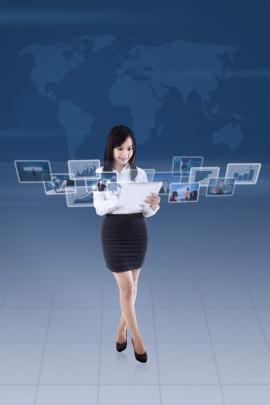 Businesswoman is looking at online pictures on e-tablet with blue world map background photo