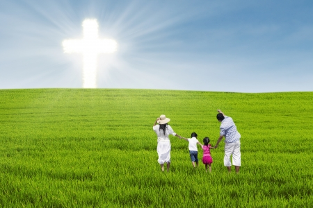 grass family: Christian family having fun on green field with cross symbol